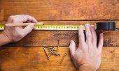 Male hand measuring wooden floor