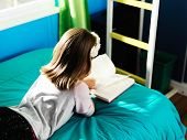 little girl on bed reading book