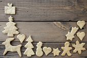 stock photo of ginger bread  - Ginger Breads Building a Frame on Wood Background with Copy Space - JPG