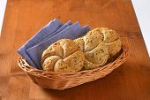 basket of fresh bread buns and blue napkin on wooden table