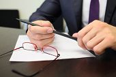 Blank sheet of paper, glasses on desk and pencil in male hands