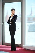 Portrait of beautiful businesswoman in black suit near large window