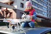 Little girl in striped hat sitting on top of car with radio control in her hands and quadcopter