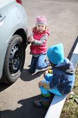 Little girl with boy tie rear wheel of car with socket wrench