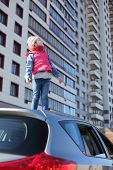 Little girl in striped hat standing on top of car and looking up