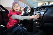 Little girl in pink waistcoat and striped hat sitting at wheel of car