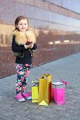 Happy little girl with pink phone and shopping bags