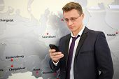 Portrait of businessman with phone leaning against wall with map