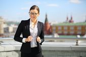 Portrait of happy beautiful businesswoman in glasses and black suit on terrace overlooking Kremlin