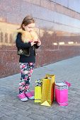 Little girl standing with pink phone and shopping bags near granite wall