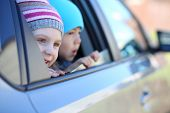 Little girl in striped hat and boy looking out car window