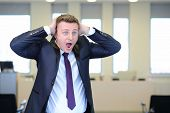 Very frightened businessman clutched his head in office