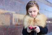 Pretty little girl dials a phone number on street