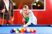 Couple or friends playing billiard with cue and balls on pool table