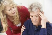 stock photo of mature men  - Mature Woman Comforting Man With Depression At Home - JPG
