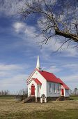 foto of red siding  - Small church in rural setting with bright red roof and red door - JPG