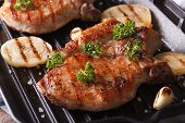 stock photo of roasted pork  - Two pork steak grilled with onions and garlic in a pan grill closeup - JPG