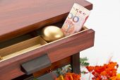 picture of nest-egg  - Chinese yuan currency and gold nest egg nestled in wood drawer