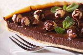 foto of tarts  - A piece of chocolate tart with hazelnut and mint on a white plate macro - JPG