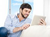 image of hispanic  - Young attractive Hispanic man at home sitting on white couch using digital tablet or pad looking relaxed smiling at living room enjoying surfing internet watching online movie - JPG