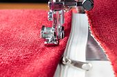 image of sewing  - sewing a white zipper on a sewing machine. sewing process