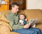 foto of settee  - Young caucasian baby girl looking up at grandfather reading newspaper on settee in family room - JPG