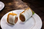 stock photo of ooze  - Sausage Cheese Rolls on white dish wood table - JPG