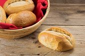stock photo of bread rolls  - single bun and bread rolls in a basket whith red napkin on a table from old wood - JPG