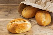 stock photo of bread rolls  - bread rolls in a paper bag on a rustic wooden table fresh from the bakery for breakfast - JPG