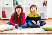 stock photo of sticking out tongue  - Little boy and little girl are sitting in living room and sticking out their tongue - JPG