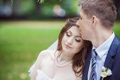foto of boutonniere  - Beautiful bride and groom sitting on a bench outdoors - JPG