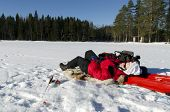picture of ice fishing  - Women lying down on ice when fishing - JPG