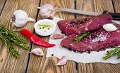 stock photo of beef shank  - Fresh beef steak on plate with aromatic spices and sauce on a wooden background - JPG
