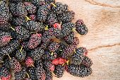 foto of mulberry  - Group of mulberries isolated on wood background - JPG