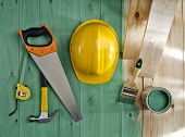 picture of sawing  - green wood floor with a brush paint saw hammer and helmet - JPG