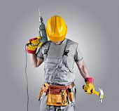 pic of hammer drill  - builder in a helmet with a hammer and a drill - JPG