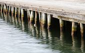 picture of rough-water  - Wharf made of wood reflecting in the water - JPG