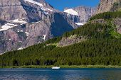 stock photo of shoreline  - a ferry boat glides along the shoreline of swiftcurrent lake glacier national park montana - JPG