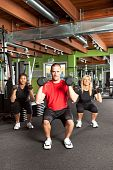 stock photo of personal trainer  - A shot of a male personal trainer training with two female athletes in the gym - JPG