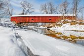 stock photo of covered bridge  - In the midst of a snowy winter landscape the historic Oakalla Covered Bridge crosses Big Walnut Creek in rural Putnam County Indiana - JPG