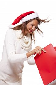 image of vivacious  - Happy vivacious Christmas shopper wearing a red Santa hat holding up a colorful red shopping bag with a beautiful beaming smile isolated on white with copyspace - JPG