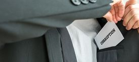 picture of corruption  - Businessman removing or placing a white card with word Corruption in the inner pocket of his suit jacket close up view of the card - JPG