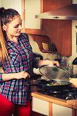 picture of stir fry  - Woman in kitchen cooking stir fry frozen vegetables - JPG