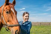 foto of beautiful horses  - Happy beautiful brunette taking care of her domestic horse outdoors - JPG