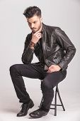 pic of down jacket  - Full body picture of a young casual man sitting on a chair while peting his beard - JPG