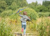 stock photo of kites  - little cute girl flying a rainbow kite in a meadow on a sunny day - JPG