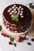 stock photo of icing  - Cherry cake with chocolate icing on a plate on a table close - JPG