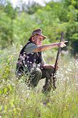 stock photo of shotgun  - Senior hunter with shotgun sitting on meadow - JPG