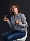 stock photo of cigar  - middle aged woman with glass of whiskey and cigar on black background - JPG