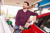 image of petrol  - Young man refuelling a car at a petrol station - JPG